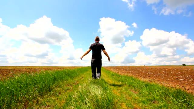 男性、腕を広げるには、ヨーロッパの美しい田園地帯春に - 後方点の映像素材/bロール