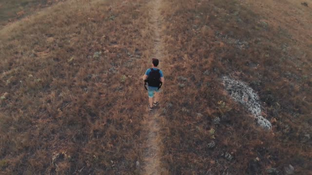Man with backpack hiking aerial view Man traveling with backpack hiking in mountains. footpath stock videos & royalty-free footage