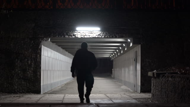Man with backpack walking through pedestrian underpass tunnel passage at night.