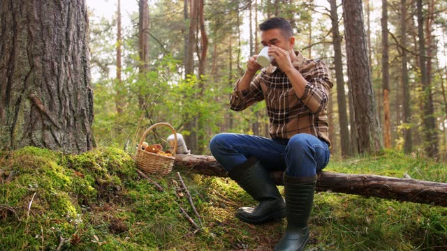 man with basket of mushrooms drinks tea in forest