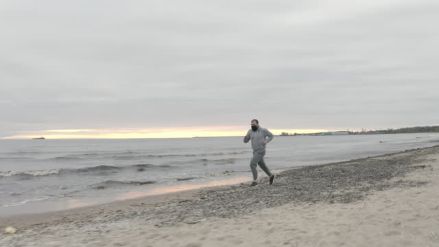 Man with Beard in Protective Face Mask Sprinting by the Beach at Dusk - Wide Dolly Shot