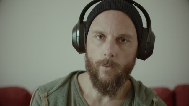 Man with beard listening music at home