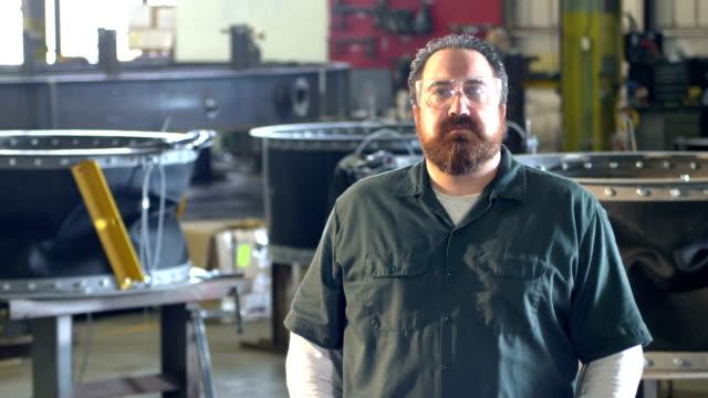 mann mit bart, der in der metallfabrik arbeitet - halle gebäude stock-videos und b-roll-filmmaterial