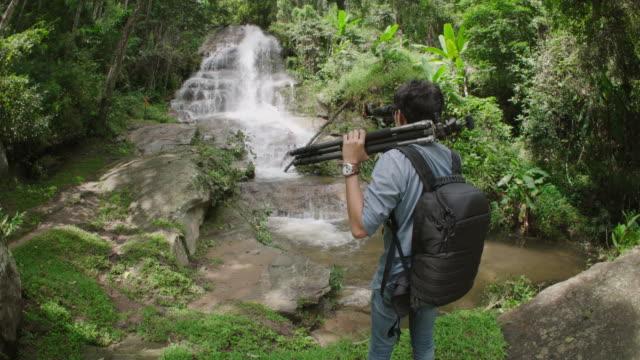 Man with binocular watching bird in nature with waterfall video