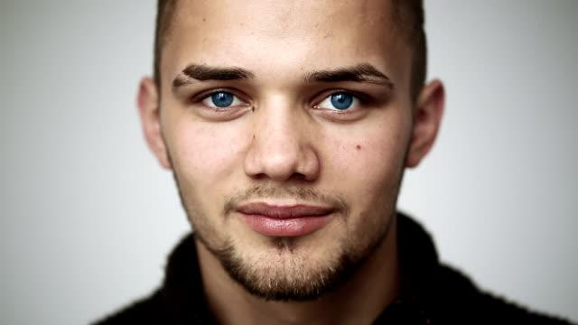 Homme aux yeux bleus et souriant montrant les dents bretelles - Vidéo