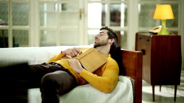 uomo con libro sonnecchiare sul divano - sonnecchiare video stock e b–roll