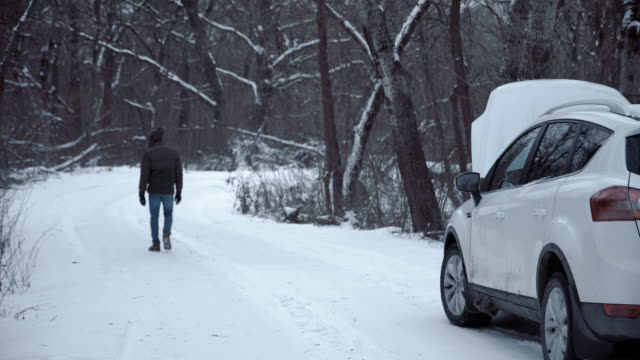 Man with broken car on winter road - video