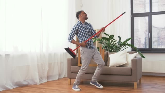 man with broom cleaning and having fun at home - vídeo