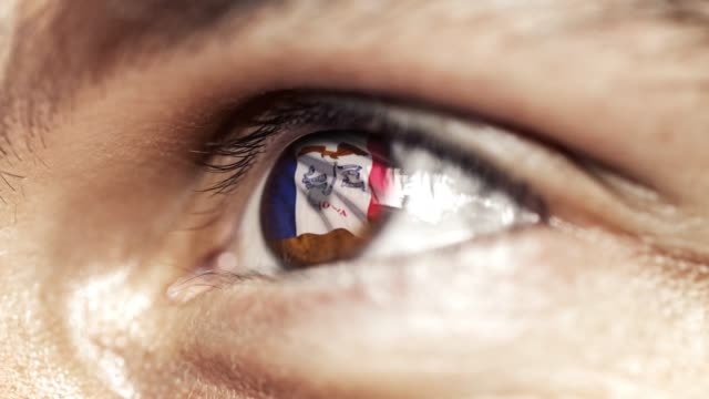 Man with brown eye in close up, the flag of Iowa state in iris, united states of america with wind motion. video concept