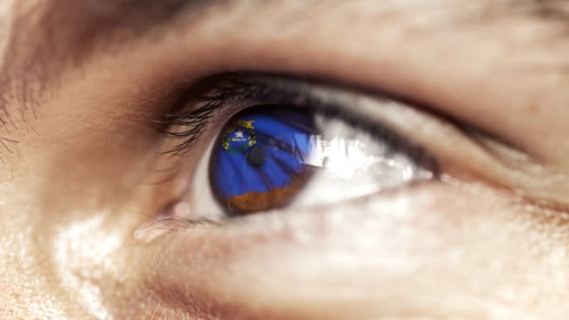 Man with brown eye in close up, the flag of Nevada state in iris, united states of america with wind motion. video concept
