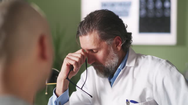 Man with cancer crying and speaking with doctor