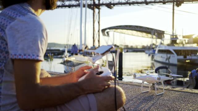 vídeos de stock e filmes b-roll de man with controller of drone on embankment - man joystick