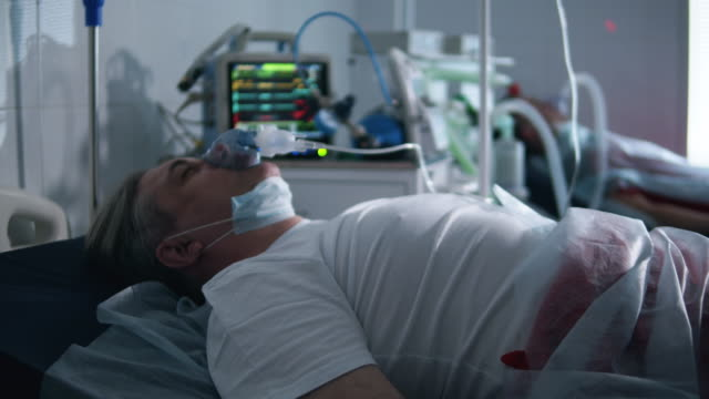 vídeos de stock e filmes b-roll de a man with covid-19 breathes with ventilator at clinic. - covid hospital bed respirator