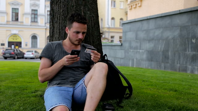 Man with credit card during shopping through internet using smart phone in park sitting under a tree video