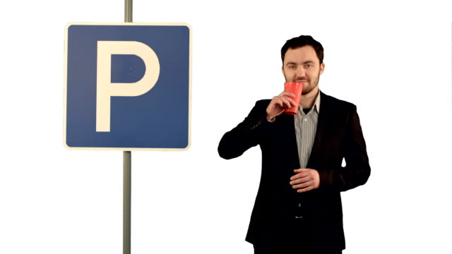 Man with cup of tea near parking sign on white background isolated video