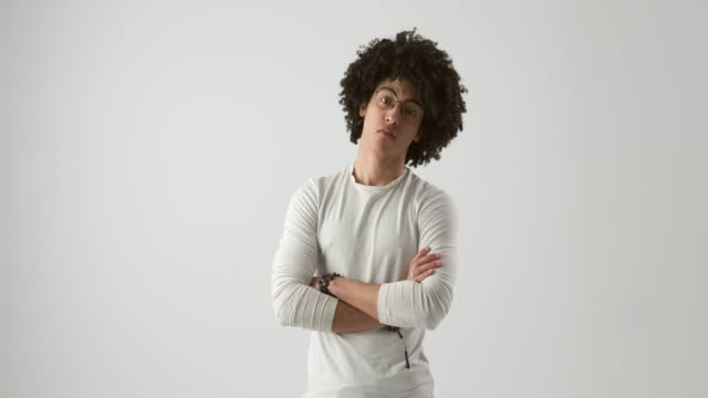 Man with curly hair posing over studio background Handsome young man with curly hair posing over white background arms akimbo stock videos & royalty-free footage