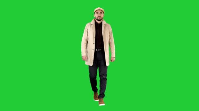 Man with dark beard in light trench coat walks on a Green Screen, Chroma Key video