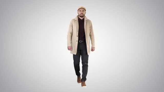 Man with dark beard in light trench coat walks on gradient background video