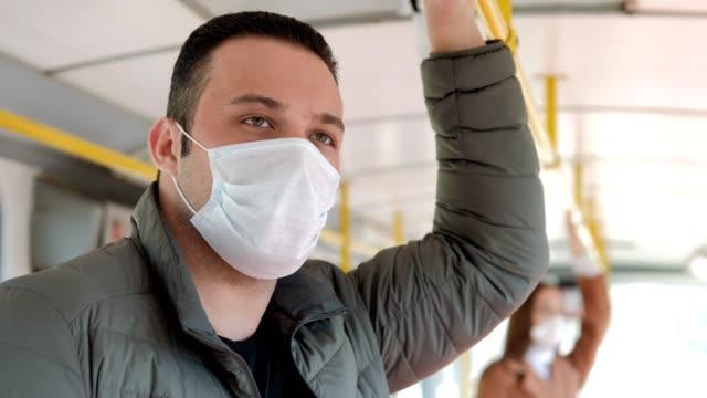 uomo con maschera usa e getta sull'autobus. protezione antivirus - autobus video stock e b–roll