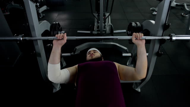 Man with elbow bandage trying lift up barbell, sport trauma, recovery therapy video