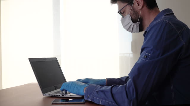 man med ansiktsmask och blåhandskar som arbetar hemifrån och orolig för covid-19 coronavirus - vpn bildbanksvideor och videomaterial från bakom kulisserna