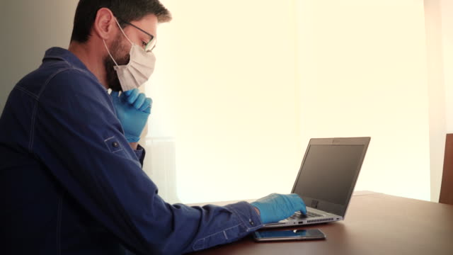 Man with face mask and blue gloves working from home and worried about covid-19 coronavirus