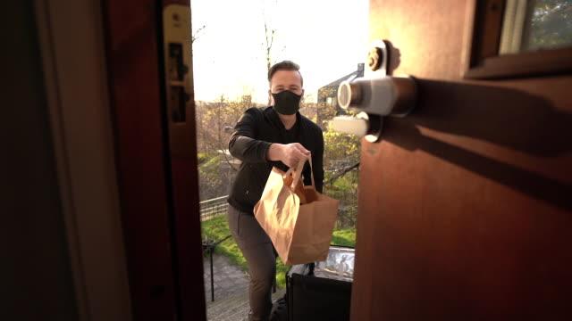 Man med ansiktsmask som levererar mat video