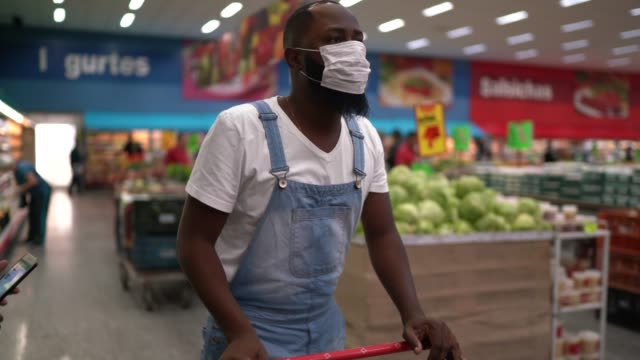 vídeos de stock e filmes b-roll de man with face mask walking and shopping in supermarket - afro latino mask