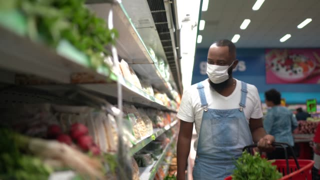 Man with face mask walking and shopping in supermarket video