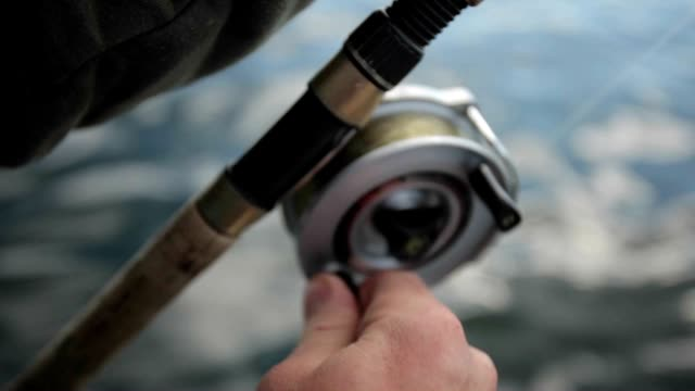 Man with fishing rod closeup Close up of man bringing fish with rod fishing rod stock videos & royalty-free footage