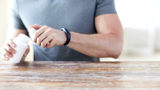 man with fitness bracelet pouring pills from jar to hand video