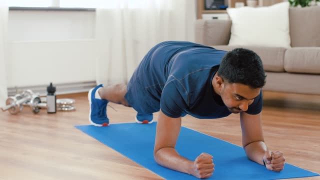 man with fitness tracker doing plank at home sport, technology and healthy lifestyle concept - indian man using fitness tracker and doing plank exercise at home bodyweight training stock videos & royalty-free footage
