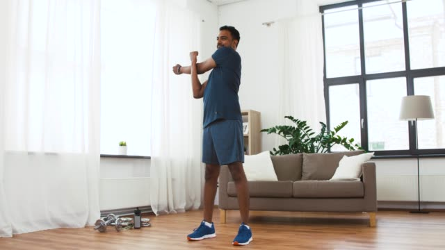 man with fitness tracker stretching body at home - активный образ жизни стоковые видео и кадры b-roll