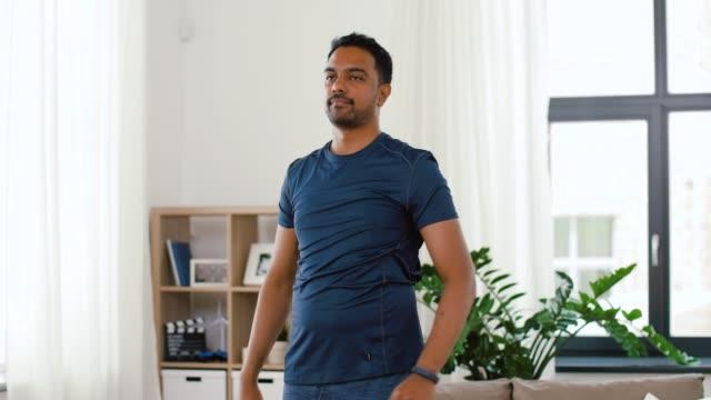vídeos de stock e filmes b-roll de man with fitness tracker stretching body at home - treino em casa