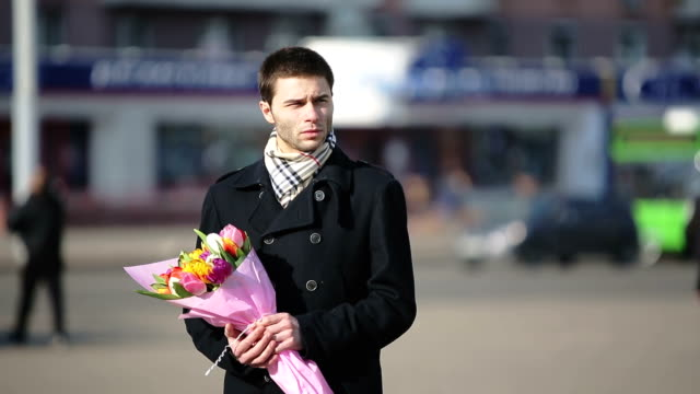 Man with flowers waiting for his woman in the city video