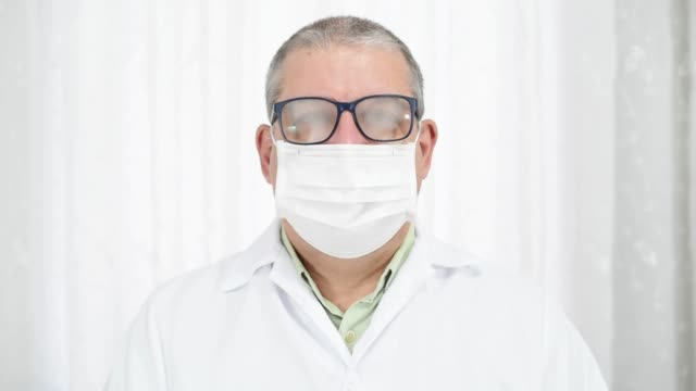 Man with fogging glasses because of wearing protective mask and smiling after that