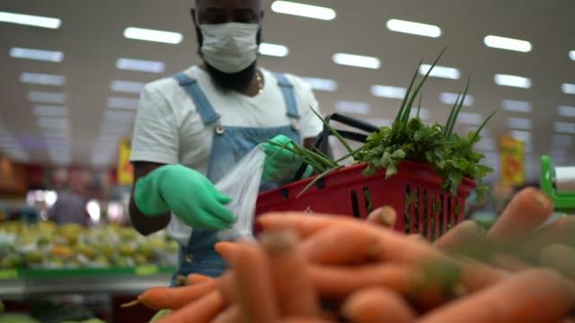 vídeos de stock e filmes b-roll de man with gloves putting carrots on plastic bag at supermarket - afro latino mask