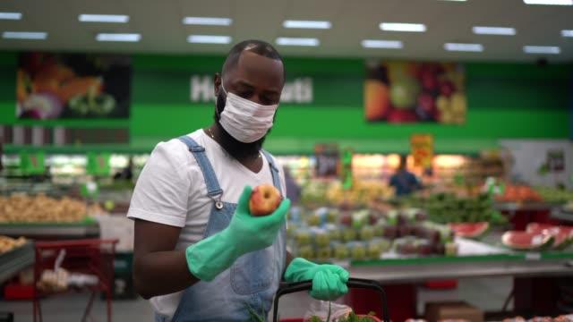 vídeos de stock e filmes b-roll de man with gloves shopping in supermarket - afro latino mask