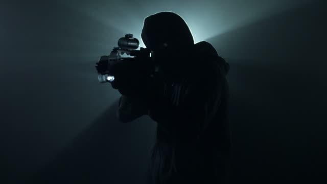 vidéos et rushes de homme avec une arme à feu dans le brouillard - mitrailleuse