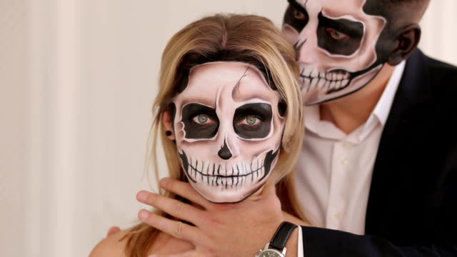 A man with Halloween makeup is holding his girlfriend by the neck. A man with a terrible make-up in the form of a zombie he hugs the girl, he puts his hand on her neck and tries to strangle her. Couple in vampire costumes in Studio. Halloween or horror concept. skull stock videos & royalty-free footage