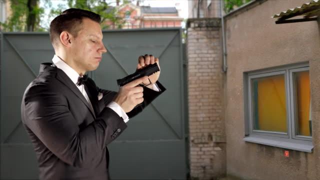 Man with Hand Gun Pistol, Cocking Hammer and Slide, Tuxedo Suit video