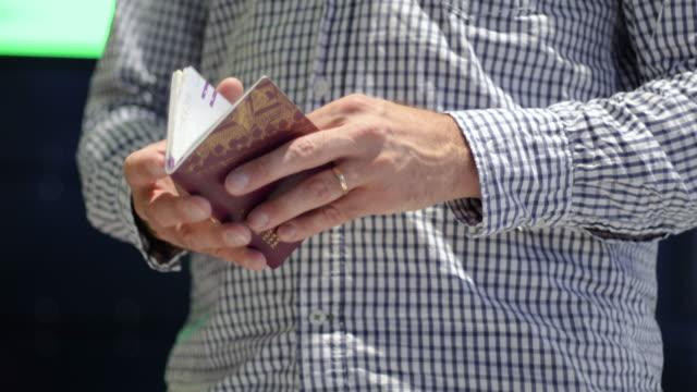 vídeos y material grabado en eventos de stock de hombre con sombrero y gafas mirando pasaporte y billete en el aeropuerto verificando la validez - pasaporte y visa