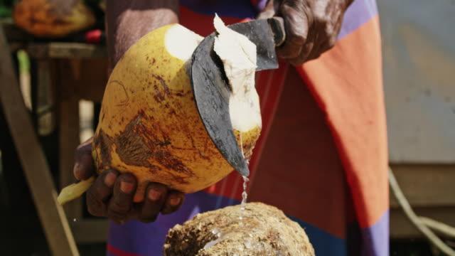 vídeos de stock e filmes b-roll de ms man with hatchet cutting fresh yellow coconut,sri lanka - sri lanka