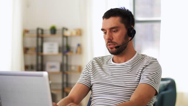 man med headset och bärbar dator som arbetar hemma - mellan 30 och 40 bildbanksvideor och videomaterial från bakom kulisserna
