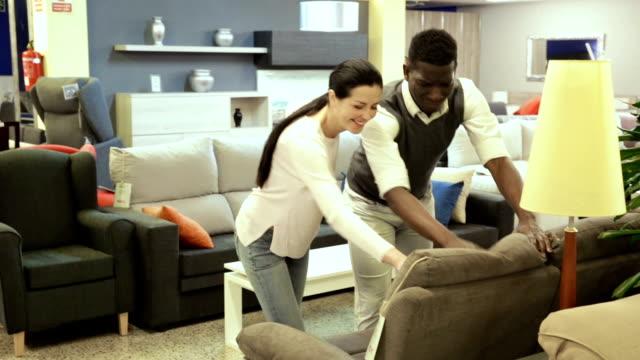 vídeos de stock, filmes e b-roll de homem com sua esposa estão escolhendo o sofá novo - mobília
