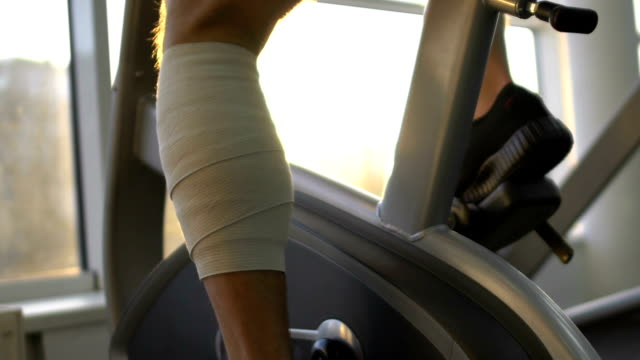 Man with injured leg riding stationary bike in morning sunlight, health recovery Man with injured leg riding stationary bike in morning sunlight, health recovery physical injury stock videos & royalty-free footage