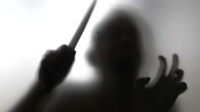 vidéos et rushes de homme avec couteau derrière verre dépoli en 4 k slow motion 60 images/s - lame