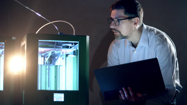 A man with laptop controls 3D printer. 3d printing industry research engineer working in lab.