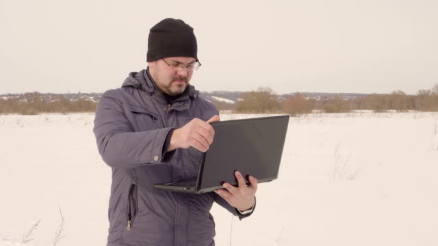 man with laptop in winter in the field - top nero video stock e b–roll
