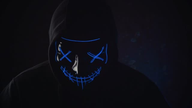 Man with lighting neon glow mask in hood raises his head and scream in camera on black background. Halloween and horror concept video